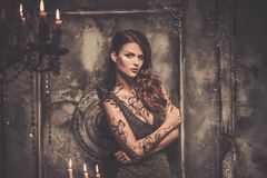 Tattooed woman in spooky interior Stock Photography