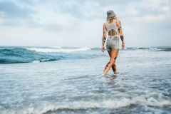 Tattooed woman walking at beach Stock Images