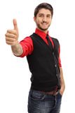 Tattooed young man making a thumb up gesture Stock Image