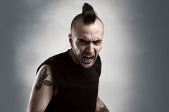 Shout. Tattooed young man with mohawk style hair screaming Royalty Free Stock Photo