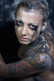 Tattooed young woman. With a creative smeared make-up Stock Images