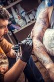 Tattooer在纹身花刺演播室做凉快的纹身花刺 免版税库存照片