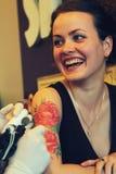 Tattooer, das Prozess der Herstellung einer Tätowierung auf junger schöner Hippie-Frau mit dem roten gelockten Haar zeigt Stockfotos
