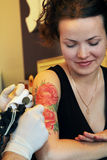 Tattooer, das Prozess der Herstellung einer Tätowierung auf junger schöner Hippie-Frau mit dem roten gelockten Haar zeigt Stockbilder