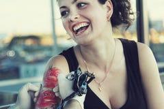 Tattooer, das Prozess der Herstellung einer Tätowierung auf junger schöner Hippie-Frau mit dem roten gelockten Haar zeigt Lizenzfreie Stockfotos
