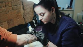 Tattooer fêmea moreno que faz a tatuagem no braço do homem de seu cliente com arma Trabalho mestre Mulher de negócio nova dentro video estoque