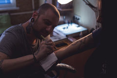 Tattooer makes scetch. Tattooer is drawing scetch on the woman's hand using spesial marker Royalty Free Stock Images