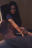 Tattooer makes scetch. Tattooer is drawing scetch on the woman's hand using spesial marker Stock Photography