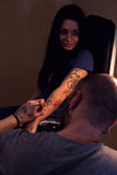 Tattooer makes scetch. Tattooer is drawing scetch on the woman's hand using spesial marker Stock Photo