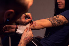 Tattooer makes scetch. Tattooer is drawing scetch on the woman's hand using spesial marker Stock Images