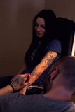 Tattooer makes scetch. Tattooer is drawing scetch on the woman`s hand using spesial marker Stock Images