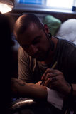 Tattooer makes scetch. Tattooer is drawing scetch on the woman`s hand using spesial marker Royalty Free Stock Images