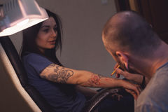Tattooer makes scetch. Tattooer is making scetch for future tattoo on the woman's hand Stock Photos