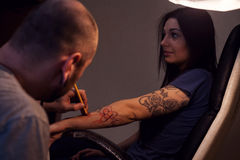 Tattooer makes scetch. Tattooer is making scetch for future tattoo on the woman`s hand Stock Photo