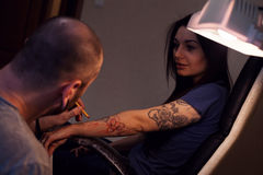 Tattooer makes scetch. Tattooer is making scetch for future tattoo on the woman`s hand Stock Photography