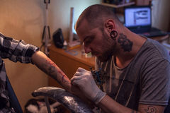 Tattooer makes tattoo for woman Royalty Free Stock Photography