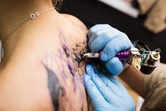 Tattooer montrant le processus de faire un tatouage, mains tenant une machine de tatoo Images libres de droits