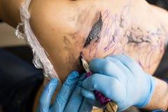 Tattooer montrant le processus de faire un tatouage, mains tenant une machine de tatoo Photographie stock libre de droits