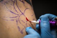 Tattooer montrant le processus de faire un tatouage, mains tenant une machine de tatoo Photographie stock