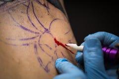 Tattooer montrant le processus de faire un tatouage, mains tenant une machine de tatoo Photo libre de droits