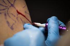 Tattooer montrant le processus de faire un tatouage, mains tenant une machine de tatoo Photos libres de droits