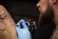 Tattooer montrant le processus de faire un tatouage, mains tenant une machine de tatoo Images stock