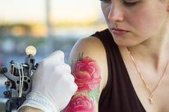 Tattooer montrant le processus de faire un tatouage sur la jeune belle femme de hippie avec le bras rouge de cheveux bouclés Conc Image stock