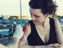 Tattooer que muestra el proceso de hacer un tatuaje en mujer hermosa joven del inconformista con el pelo rizado rojo Imagen de archivo libre de regalías