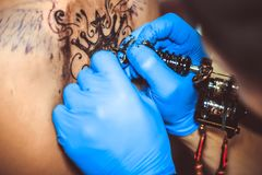 Master tattoo woman on her back. Tattooer showing process of making a tattoo hands holding a tatoo machine royalty free stock images