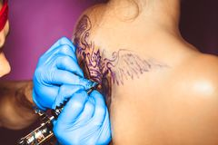 Master tattoo woman on her back. Tattooer showing process of making a tattoo hands holding a tatoo machine stock image