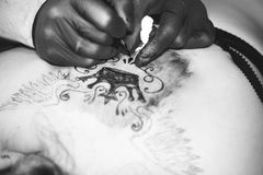 Master tattoo woman on her back. Tattooer showing process of making a tattoo hands holding a tatoo machine royalty free stock image
