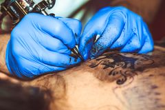 Master tattoo woman on her back. Tattooer showing process of making a tattoo hands holding a tatoo machine royalty free stock photo