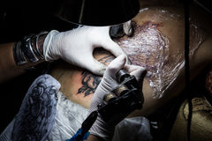 Tattooer showing process of making a tattoo. Tattoo design Royalty Free Stock Photos