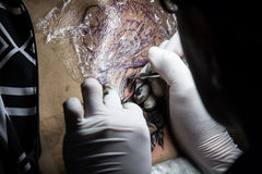 Tattooer showing process of making a tattoo. Tattoo design Stock Images