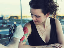 Tattooer showing process of making a tattoo on young beautiful hipster woman with red curly hair. Tattoo design in the form of rose. Vintage picture royalty free stock image
