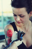 Tattooer showing process of making a tattoo. On young beautiful hipster women with red curly hair. Tattoo design in the form of rose stock image