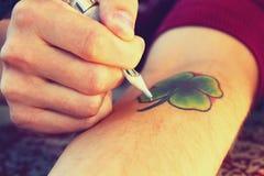 Tattooer visningprocess av att göra en tatuering Arkivbild