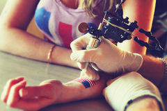 Tattooer visningprocess av att göra en tatuering på ung härlig hipsterkvinna Royaltyfri Fotografi