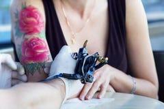 Tattooer visningprocess av att göra en tatuering på ung härlig hipsterkvinna med den röda armen för lockigt hår Tatueringdesign i Royaltyfri Foto