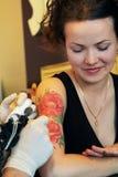 Tattooer visningprocess av att göra en tatuering på ung härlig hipsterkvinna med rött lockigt hår Arkivbilder
