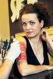 Tattooer visningprocess av att göra en tatuering på ung härlig hipsterkvinna med rött lockigt hår Arkivfoton
