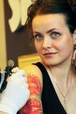 Tattooer visningprocess av att göra en tatuering på ung härlig hipsterkvinna med rött lockigt hår Royaltyfri Bild