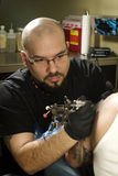 Tattooing a clients arm. Concentrated young tattooer tattooing a clients arm Stock Photo