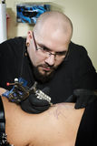 Tattooing on the side of clients abdomen. In tattoo shop Royalty Free Stock Image