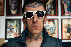 Tattooist in denim vest and sunglasses Stock Images
