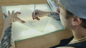 Tattooist draws the sketch on the tracing paper on the glass with light. The tattoo artist puts the drawing on the tracing paper. Ready sketch of tattoo is stock footage