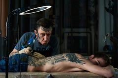 Tattooist makes faces Stock Photos