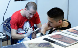 Tattooist makes a tattoo on his client's on 18 April, 2015, Sofia, Bulgaria Royalty Free Stock Image