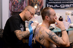Tattooist makes a tattoo on his client's on 18 April, 2015, Sofia, Bulgaria Stock Image