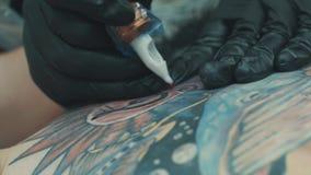 Tattooist que hace un tatuaje en la parte posterior del ` s de la muchacha almacen de metraje de vídeo
